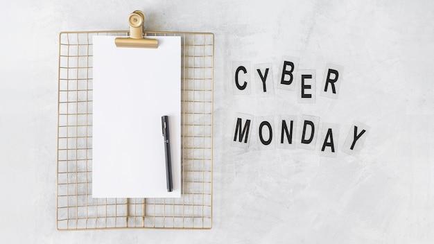 Prancheta com papel perto de inscrição cyber segunda-feira