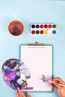 Prancheta com tintas aquarela na caixa, nas mãos de pincéis e paleta em azul