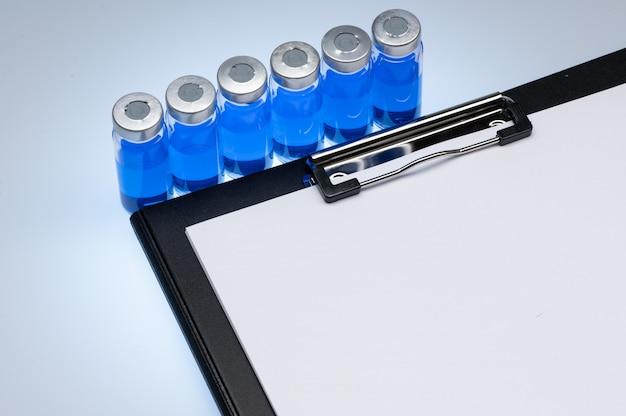 Prancheta com uma folha de papel branca para a inscrição e um frasco de vacina em uma superfície branca