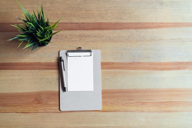 Prancheta da vista superior com pena e livro branco no fundo da tabela.
