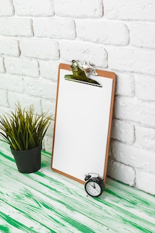 Prancheta de madeira de escritório em pé contra a parede de tijolos brancos, copie o espaço