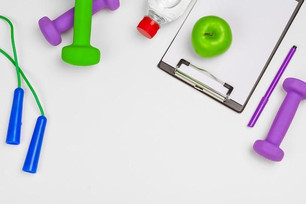 Prancheta de maquete com halteres de equipamentos de ginástica em branco