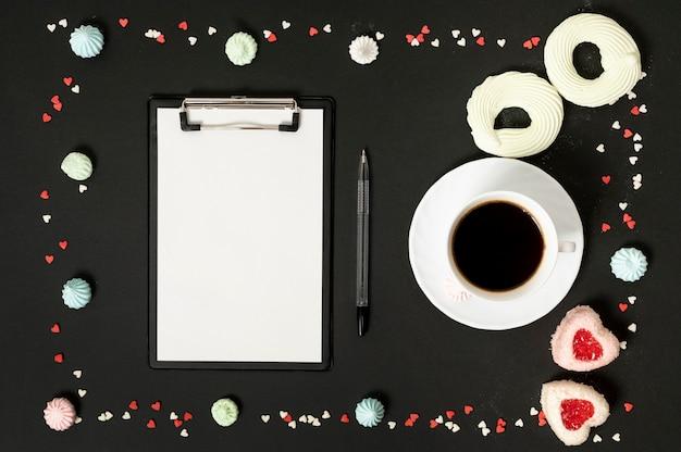 Prancheta de mock-up com uma xícara de café, cercada por biscoitos de merengue