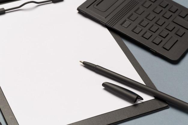 Prancheta de notas com caneta, calculadora e folhas de papel em branco