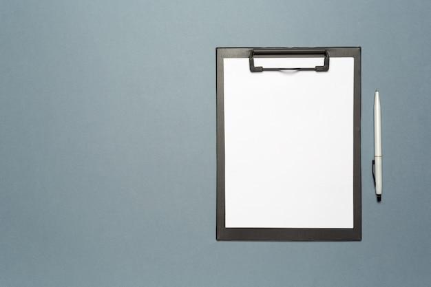 Prancheta de notas com caneta e folhas de papel em branco como mock up cópia espaço, vista superior