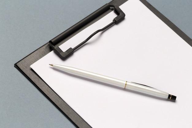 Prancheta de notas com caneta e folhas de papel em branco