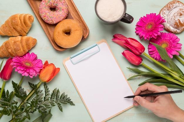 Prancheta de quadro com escrita de mão e café da manhã