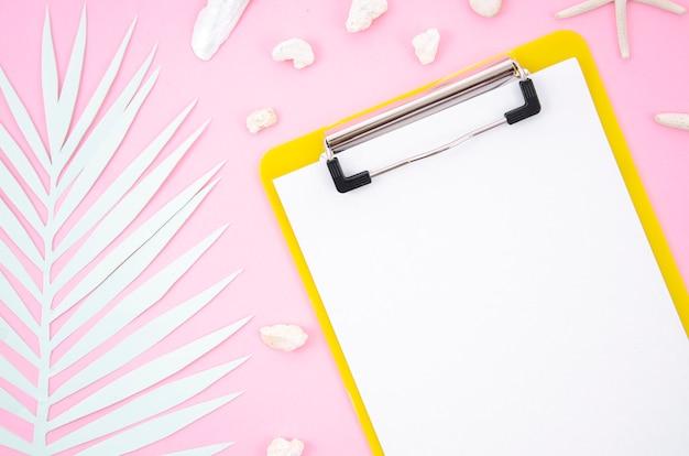 Prancheta de vista superior com um pedaço de papel em branco e folha de palmeira em fundo rosa