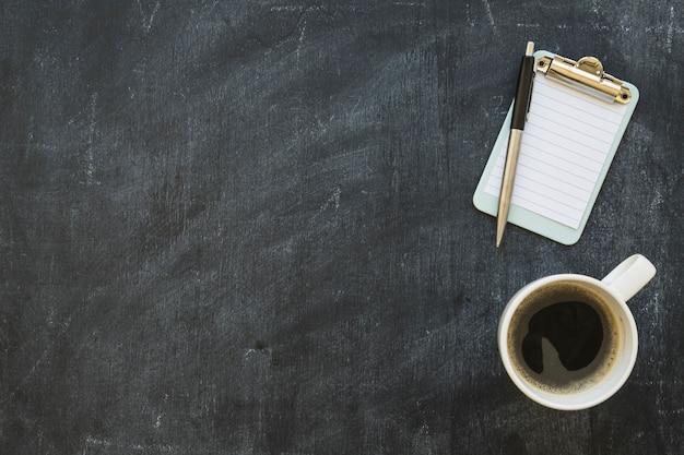 Prancheta diminuta com caneta e xícara de café no quadro-negro