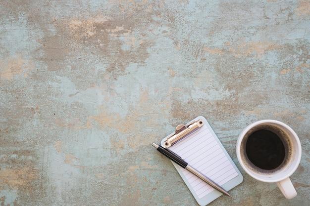 Prancheta diminuta com copo da pena e de café no fundo rústico