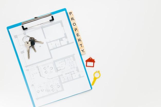 Prancheta do blueprint; chave de casa e bloco de propriedade com pano de fundo branco copyspace