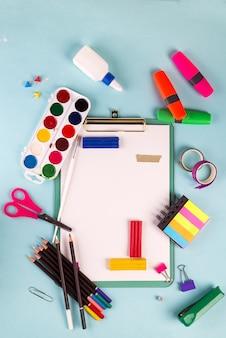 Prancheta e escritório ou material escolar sobre o azul, de volta à escola
