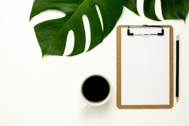 Prancheta e livro branco no fundo branco da mesa de escritório. flat lay design.