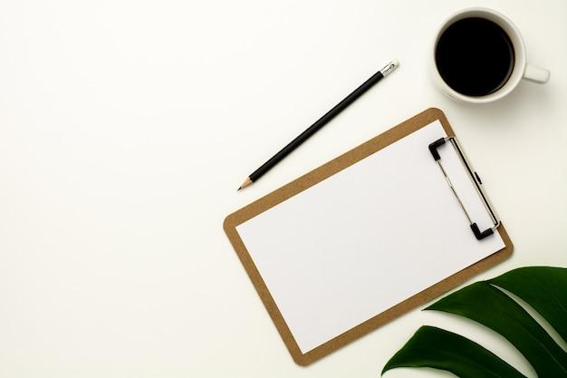 Prancheta e livro branco no fundo branco da mesa de escritório.