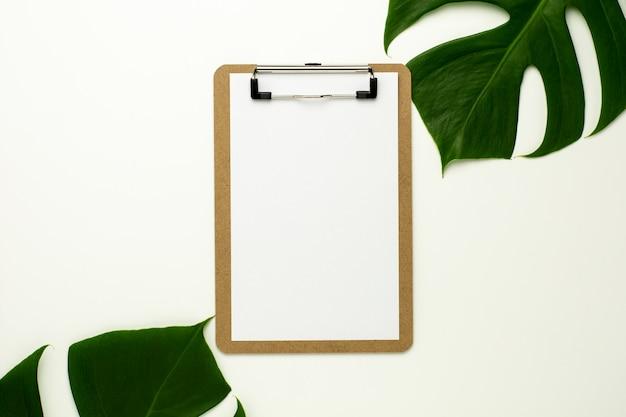 Prancheta e papel branco sobre fundo branco de mesa de escritório