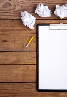 Prancheta e um lápis, na velha mesa de madeira suja.