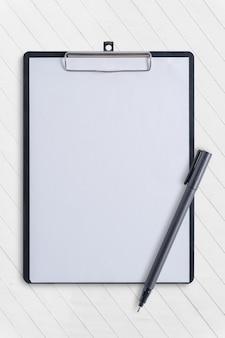 Prancheta em branco e caneta na mesa de concreto branco