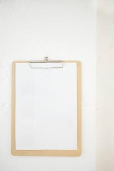 Prancheta em branco na parede branca.