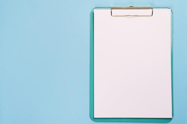 Prancheta em branco sobre fundo de cor azul pastel com espaço de cópia, plana leigos