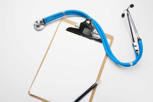 Prancheta médica em branco com estetoscópio no fundo branco