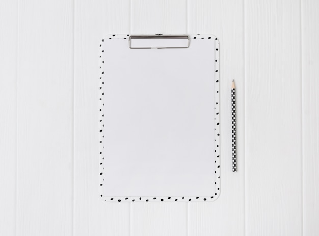 Prancheta moderna com folha em branco e lápis sobre uma mesa de madeira branca.