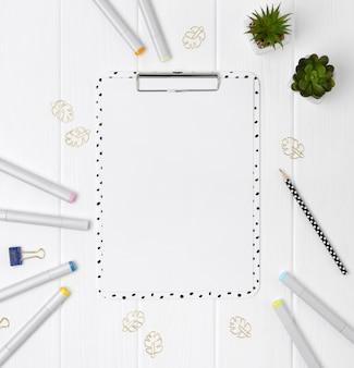 Prancheta moderna com folha em branco e marcadores, clip, aglutinantes de fita adesiva e plantas em uma mesa de madeira branca.