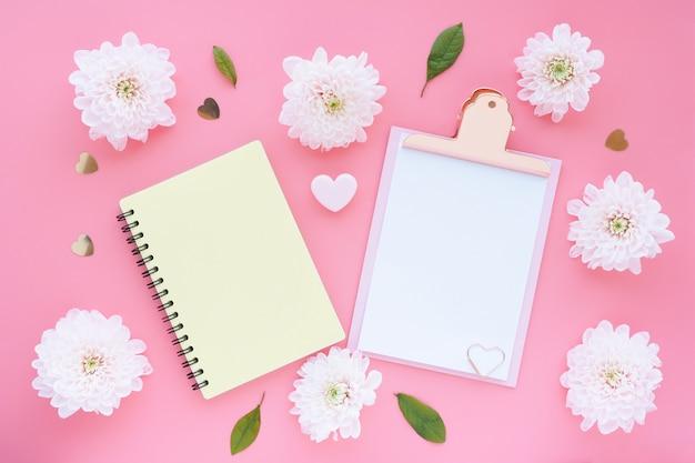 Prancheta rosa, bloco de notas amarelo em um coração de primavera e flores cor de rosa em uma mesa rosa. layout plano, vista superior.