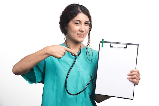 Prancheta vazia com caneta nas mãos de uma médica em fundo branco. foto de alta qualidade