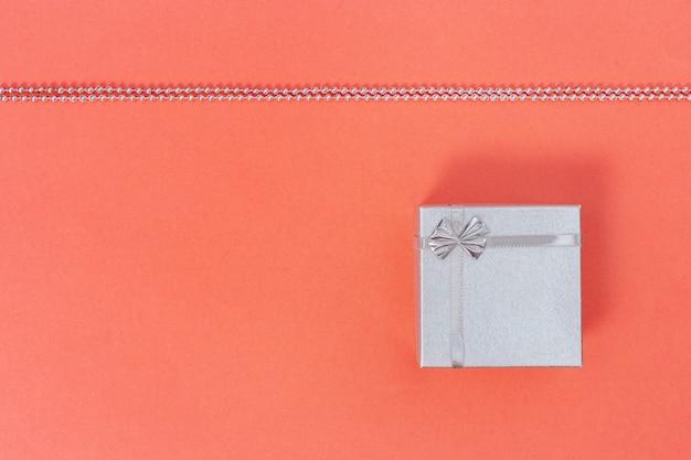 Prata brilhante caixa de presente fechado no coral vivo do fundo de papel colorido. composição de estilo minimalista.