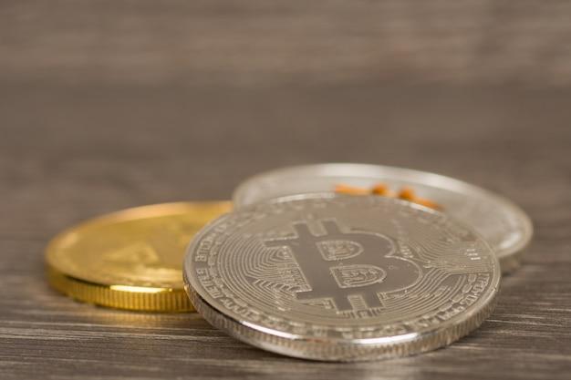 Prata e ouro moedas de criptomoeda metálica na mesa de madeira