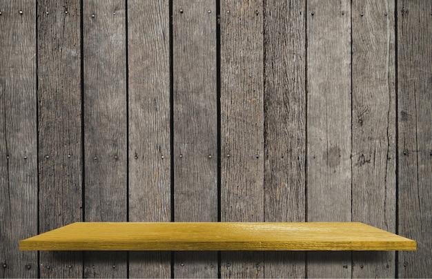 Prateleira amarela vazia no fundo de madeira para exposição do produto