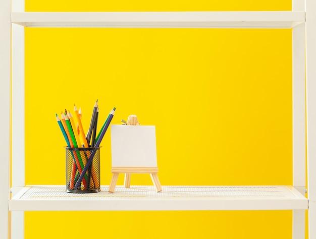 Prateleira branca com objetos de papelaria contra amarelo brilhante
