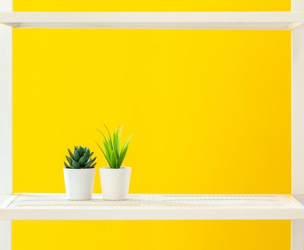 Prateleira branca com objetos de papelaria contra fundo amarelo brilhante