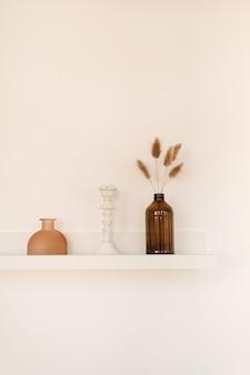 Prateleira branca na parede branca com garrafa, vaso, plantas fofas de pom pom, castiçal.