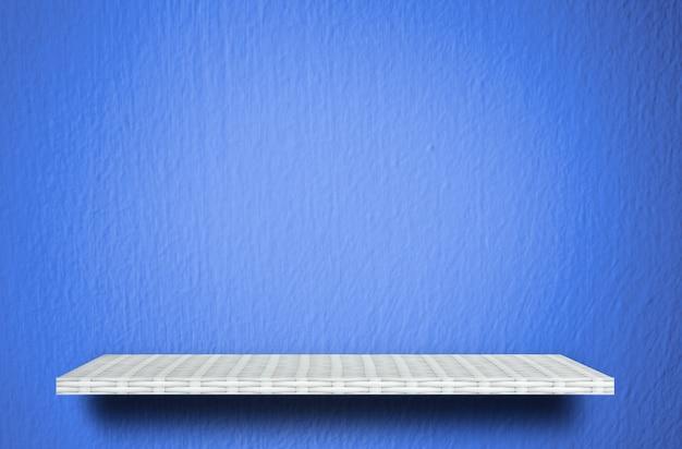 Prateleira branca vazia no fundo azul do cimento para a exposição do produto