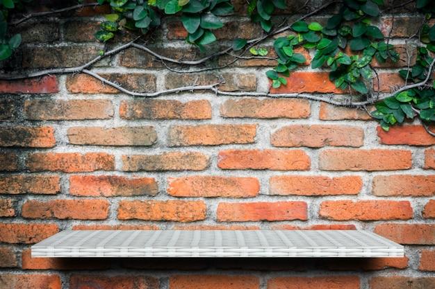 Prateleira branca vazia no fundo da parede do jardim de tijolo para exposição do produto