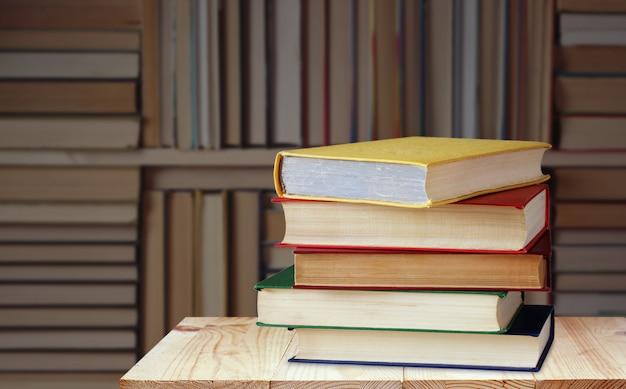 Prateleira com livros contra o fundo desfocado da biblioteca