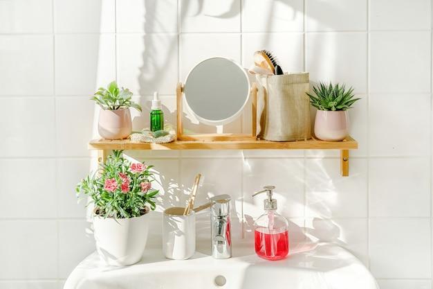 Prateleira de bambu com amenidades de banho em banheiro branco moderno