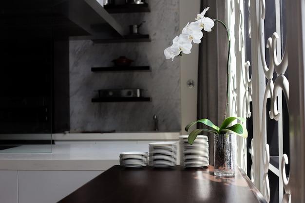 Prateleira de decoração de cozinha com flor de orquídea perto de janelas
