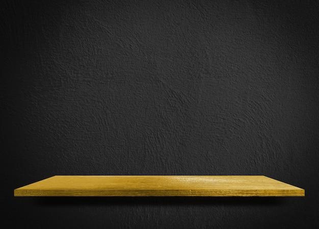Prateleira de madeira amarela na tabela de prateleira de exposição de produto de parede de cimento preto