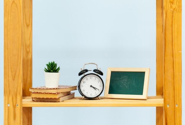Prateleira de madeira com despertador e objetos contra azul