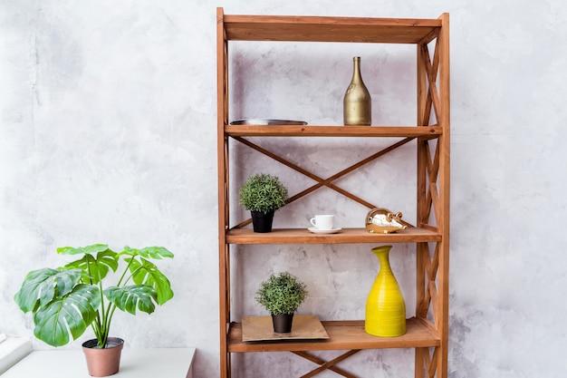 Prateleira de madeira com elementos decorativos e planta em vaso apoiada em parede cinza. foto horizontal