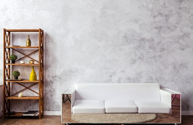 Prateleira de madeira com elementos decorativos e um sofá de couro branco encostado a uma parede cinza. foto horizontal