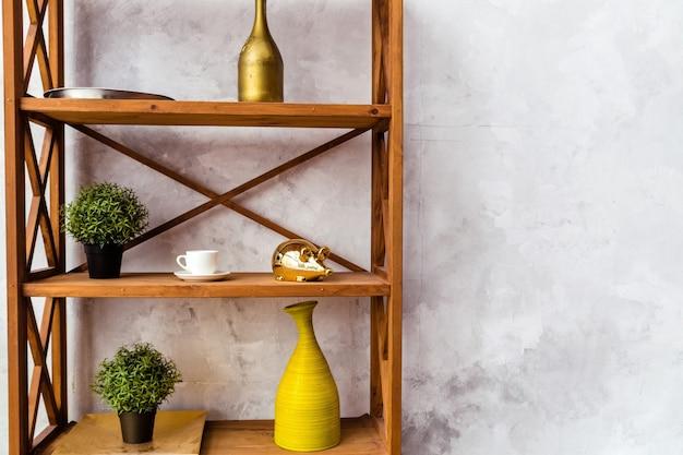 Prateleira de madeira com elementos decorativos e vasos de plantas encosta a uma parede cinza. foto horizontal