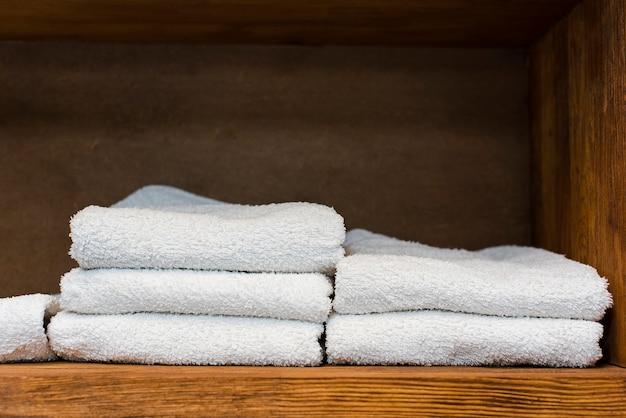 Prateleira de madeira com toalhas brancas limpas