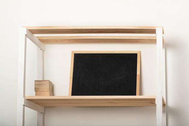 Prateleira de madeira e quadro de giz sobre fundo claro. interior em tons pastel. copie o espaço