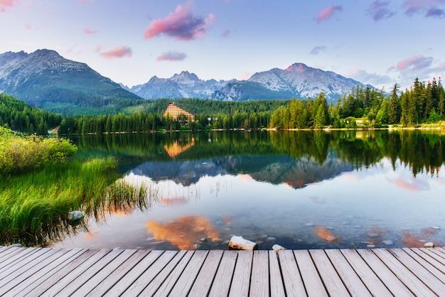 Prateleira de madeira para apresentação do produto, com plano de fundo do lago strbske pleso na montanha tatras alta, eslováquia