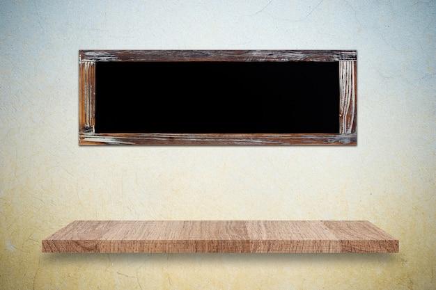 Prateleira de madeira vazia e lousa na parede de cimento