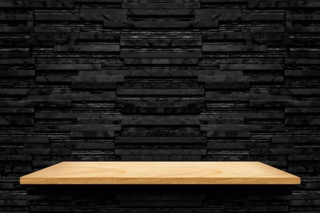 Prateleira de madeira vazia no fundo da parede de azulejo de mármore de camada preta