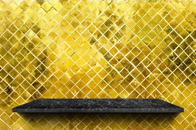 Prateleira de mármore preta vazia no fundo da parede de azulejo de mosaico de ouro brilho
